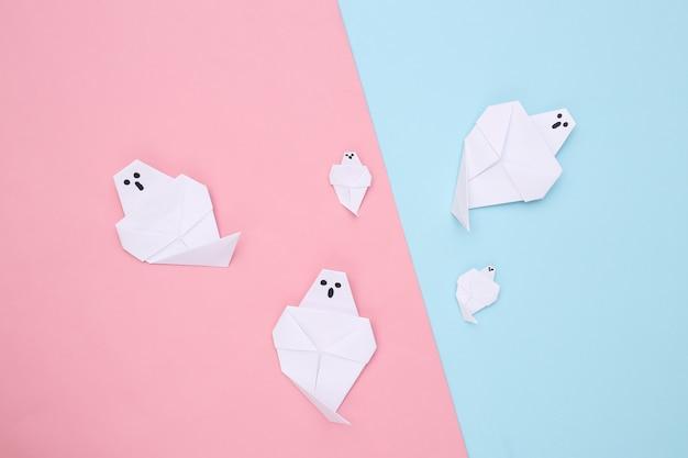 Fantasmas de origami em fundo azul rosa. decoração artesanal de halloween. vista do topo