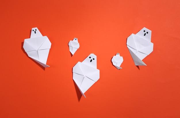 Fantasmas de origami em fundo laranja brilhante. decoração artesanal de halloween. vista do topo