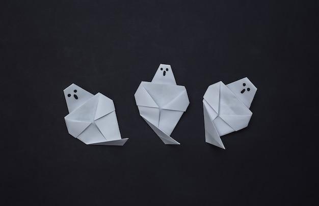 Fantasmas de origami em fundo preto. decoração artesanal de halloween. vista do topo