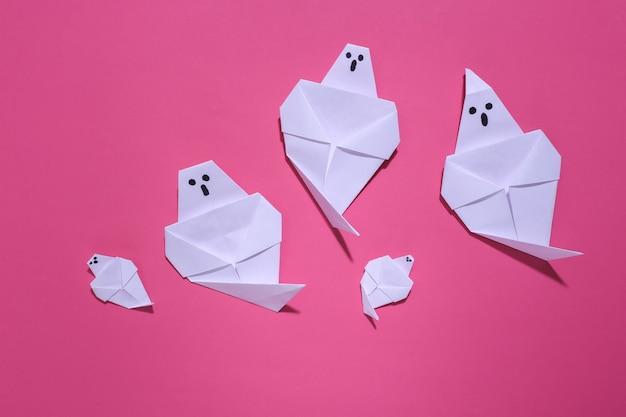 Fantasmas de origami em fundo rosa brilhante. decoração artesanal de halloween. vista do topo
