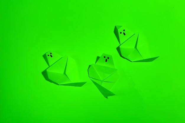 Fantasmas de origami em luz neon verde. tema de halloween