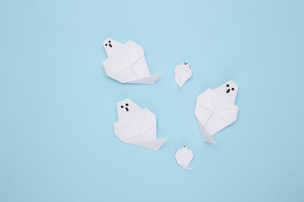 Fantasmas de origami em um fundo azul. decoração artesanal de halloween. vista do topo