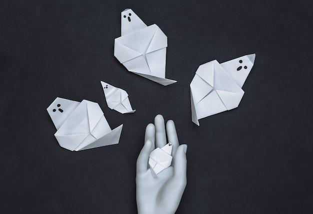 Fantasmas de origami feito à mão e mão de manequim em fundo preto. tema de halloween. vista do topo