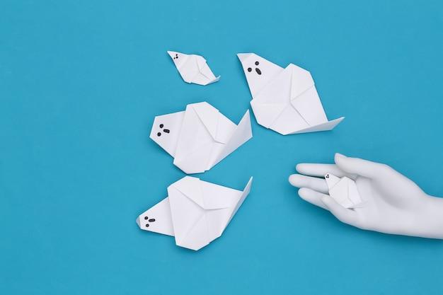 Fantasmas de origami feito à mão e mão de manequim sobre fundo azul. tema de halloween. vista do topo