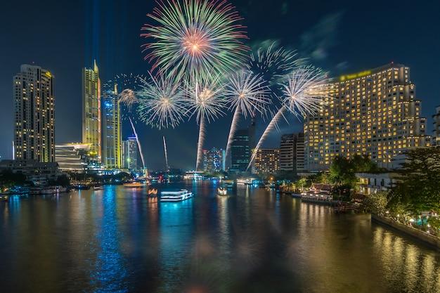 Fantastic multicolor firework explodindo sobre o lado do rio bangkok cityscape para celebrat