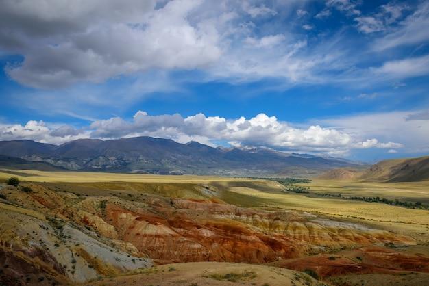 Fantástica paisagem montanhosa deserta em dia ensolarado. rochas coloridas sob um céu azul com nuvens brancas.