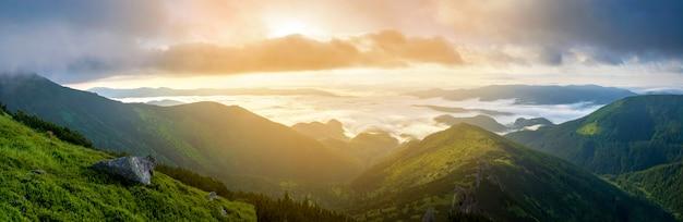 Fantástica vista do vale da montanha coberto com baixo branco inchado como nuvens de neve que se estendem até o horizonte nebuloso sob o céu da manhã brilhante com brilho laranja claro ao amanhecer. beleza do conceito de natureza.