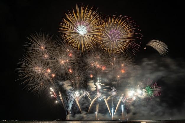 Fantástico fogo de artifício multicolor explodindo para celebração do grande barco sobre o mar
