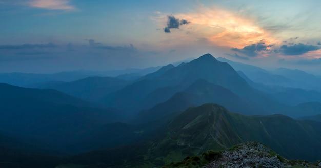 Fantástico nascer ou pôr do sol sobre o cume da montanha verde coberto com densa névoa azul. sol laranja brilhante, elevando-se no céu nublado suave ao longo do horizonte distante. beleza da natureza, turismo e conceito de viagem.