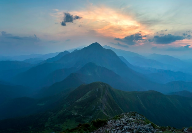 Fantástico nascer ou pôr do sol sobre o cume da montanha verde coberto com densa névoa azul. sol laranja brilhante, elevando-se no céu nublado suave, no horizonte distante beleza da natureza, turismo e conceito de viagem.