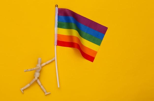 Fantoche de wodden segurando a bandeira do arco-íris lgbt em fundo amarelo. tolerância, liberdade, parada gay