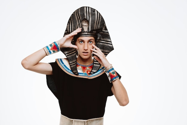 Faraó egípcio em traje egípcio antigo olhando para a frente confuso e surpreso de pé sobre uma parede branca