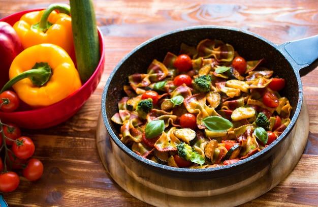 Farfalle de massa italiana em molho de tomate e vários tipos de legumes em uma mesa de madeira