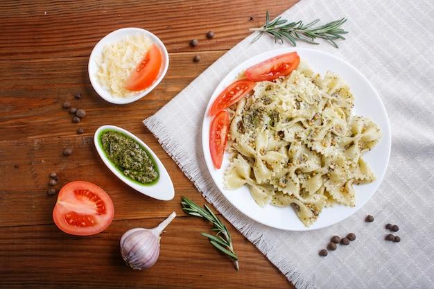 Farfalle macarrão com molho pesto, tomate e queijo numa toalha de mesa de linho em madeira de castanho