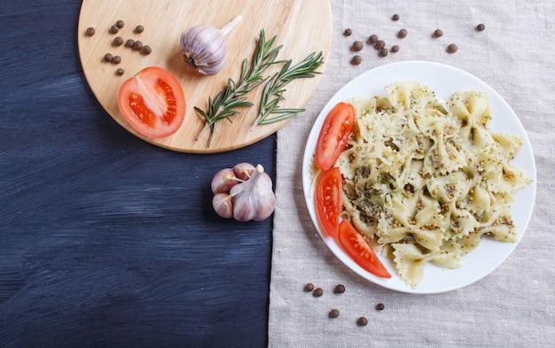Farfalle macarrão com molho pesto, tomate e queijo numa toalha de mesa de linho em preto