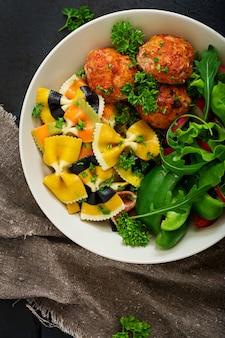 Farfalle macarrão de trigo duro com almôndegas assadas de filé de frango em molho de tomate e salada na tigela.