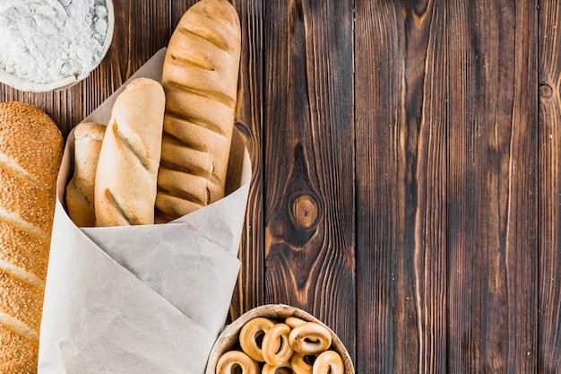 Farinha, baguetes e bagels no fundo de madeira