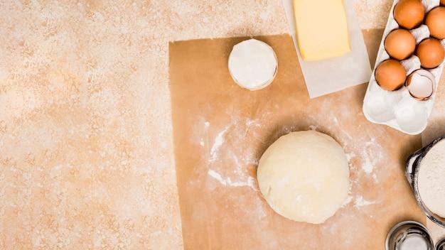 Farinha; bloco de manteiga; ovos e bola de massa no balcão da cozinha sobre papel pergaminho