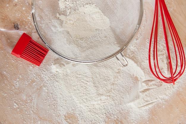 Farinha branca e ferramentas de silicone vermelho na tábua de madeira