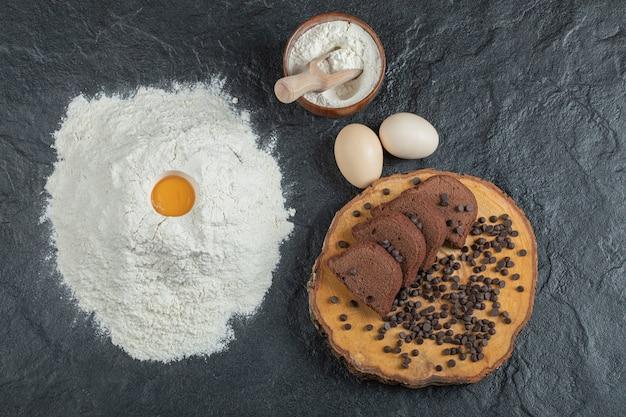 Farinha com gema de ovo, ovos e rodelas de bolo em superfície escura.