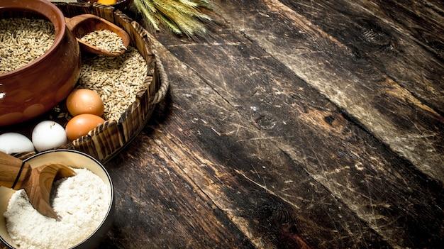 Farinha com grãos de trigo em uma bandeja velha. sobre um fundo de madeira.