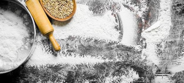 Farinha com peneira, o grão e o rolo na mesa rústica