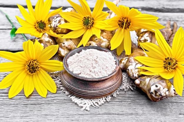 Farinha de alcachofra de jerusalém em uma tigela de barro sobre uma serapilheira com flores amarelas e vegetais no fundo da placa de madeira