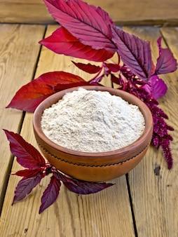 Farinha de amaranto em uma tigela de barro e flor de amaranto roxa no fundo de tábuas de madeira