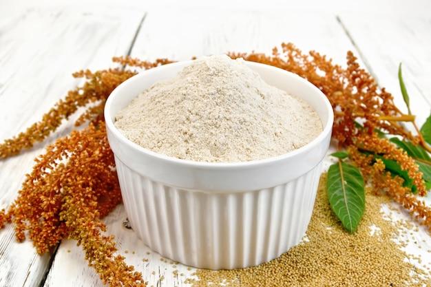 Farinha de amaranto em uma tigela, sementes espalhadas na mesa, flor marrom com folhas no fundo de tábuas de madeira