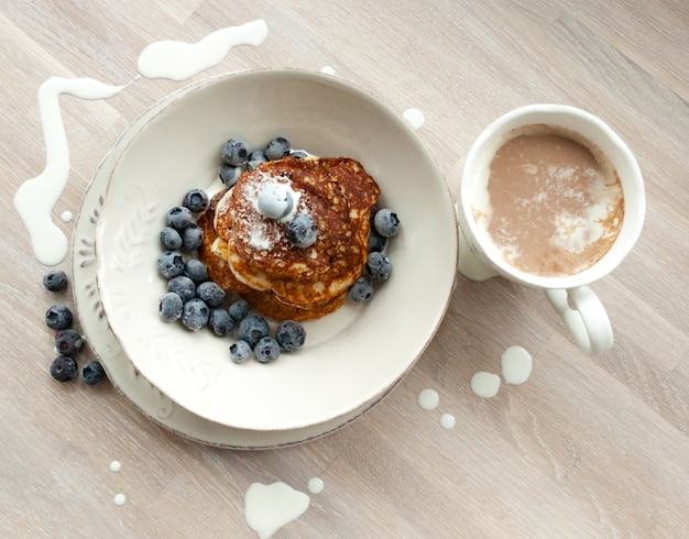 Farinha de amêndoa e coco com dieta baixa em carboidratos keto panquecas com mirtilos, creme, prato branco, xícara de cacau