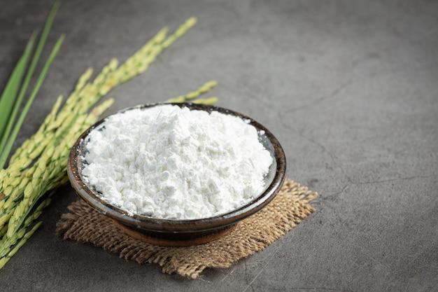 Farinha de arroz branco em uma tigela pequena com planta de arroz