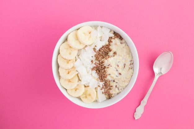Farinha de aveia ao leite com sementes de linho, banana e lascas de coco na tigela branca