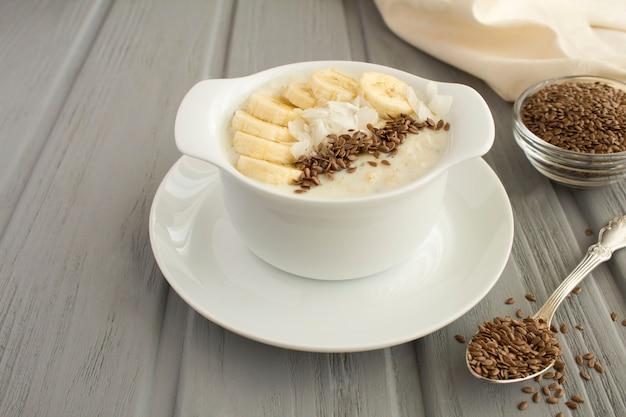 Farinha de aveia ao leite com sementes de linho, banana e lascas de coco