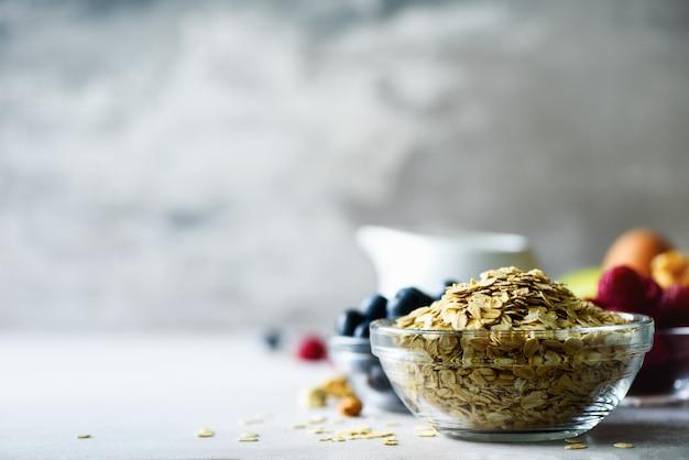 Farinha de aveia, aveia flocos em fundo cinza de concreto. conceito de pequeno-almoço saudável.