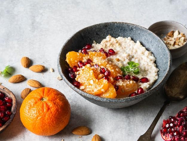 Farinha de aveia com fatias frescas de tangerina e sementes de romã, amêndoas moídas e hortelã em uma tigela azul sobre fundo branco.