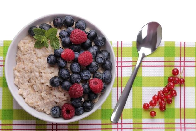 Farinha de aveia com frutas em uma tigela sobre fundo branco isolado. café da manhã. comida saudável