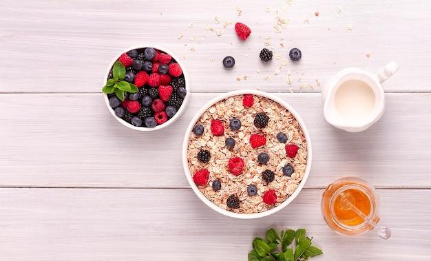 Farinha de aveia com frutas vermelhas, vista de cima, café da manhã saudável, sobre uma mesa branca, sem pessoas. foto de alta qualidade