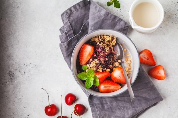 Farinha de aveia cozida com bagas e leite em uma bacia cinzenta, vista superior. café da manhã vegano.