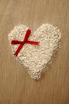 Farinha de aveia da forma do coração no fundo de madeira. bom para o conceito de comida saudável