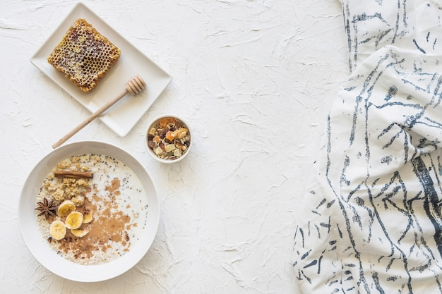 Farinha de aveia; dryfruits e favo de mel com lenço no plano de fundo texturizado