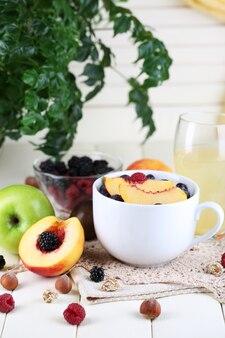 Farinha de aveia em copo com frutas em guardanapos na mesa de madeira no brilhante