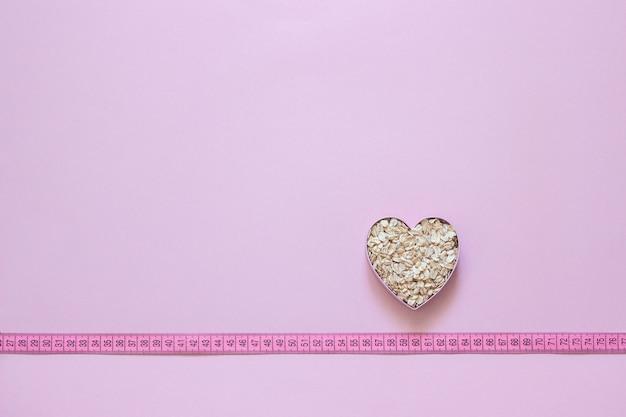 Farinha de aveia em forma de coração na fita métrica em fundo rosa.