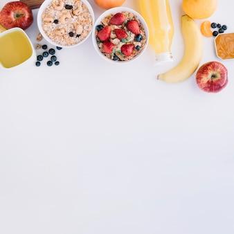 Farinha de aveia em taças com diferentes frutas na mesa