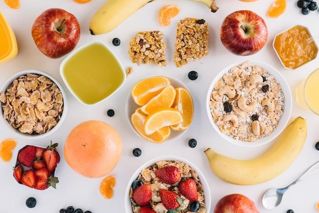 Farinha de aveia em taças com frutas e bagas na mesa branca