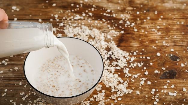 Farinha de aveia em uma tigela. o leite está sendo derramado em uma tigela sobre uma superfície de madeira. café da manhã saudável