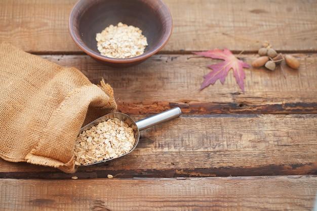 Farinha de aveia ou flocos de aveia na mesa de madeira.