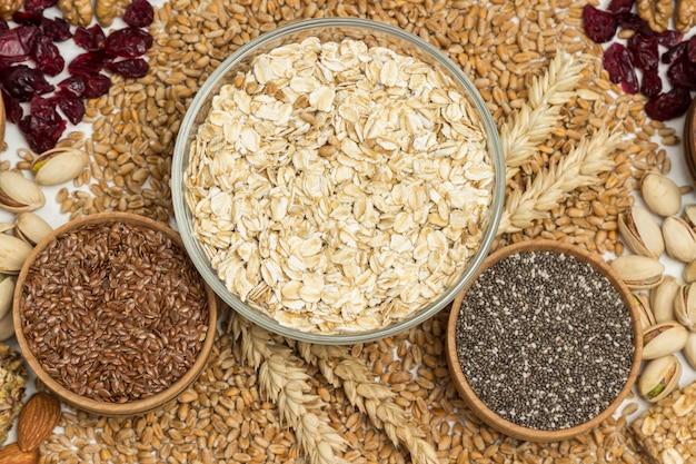 Farinha de aveia, sementes de linho, quinua. grãos de trigo e espigas de trigo, nozes, passas.