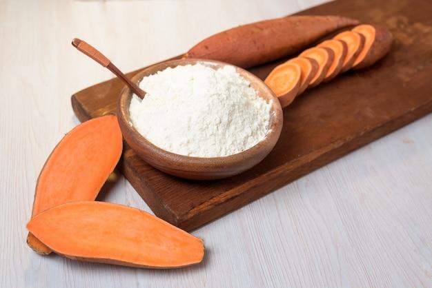 Farinha de batata doce em uma placa de madeira sobre um fundo claro. batata doce fresca cortada em pedaços de laranja ao lado da farinha