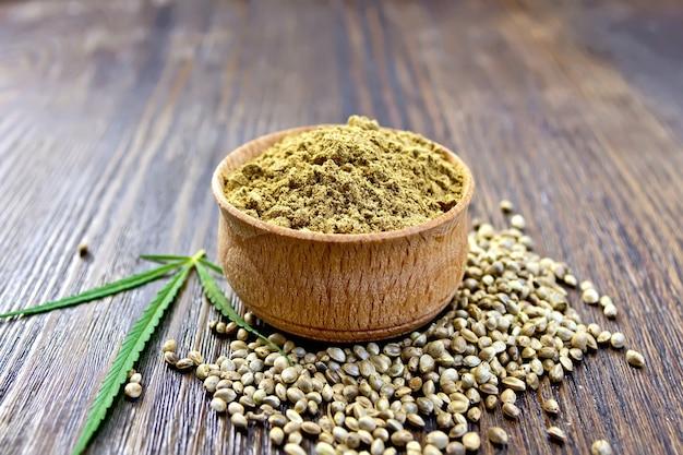 Farinha de cânhamo em uma tigela, milho e folhas verdes de cânhamo em um fundo de pranchas de madeira