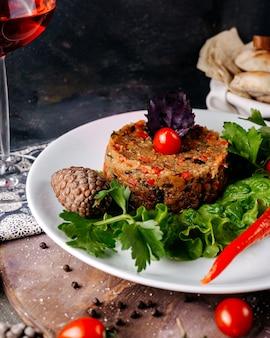 Farinha de carne, juntamente com salada verde e tomate cereja vermelho dentro de chapa branca na superfície cinza